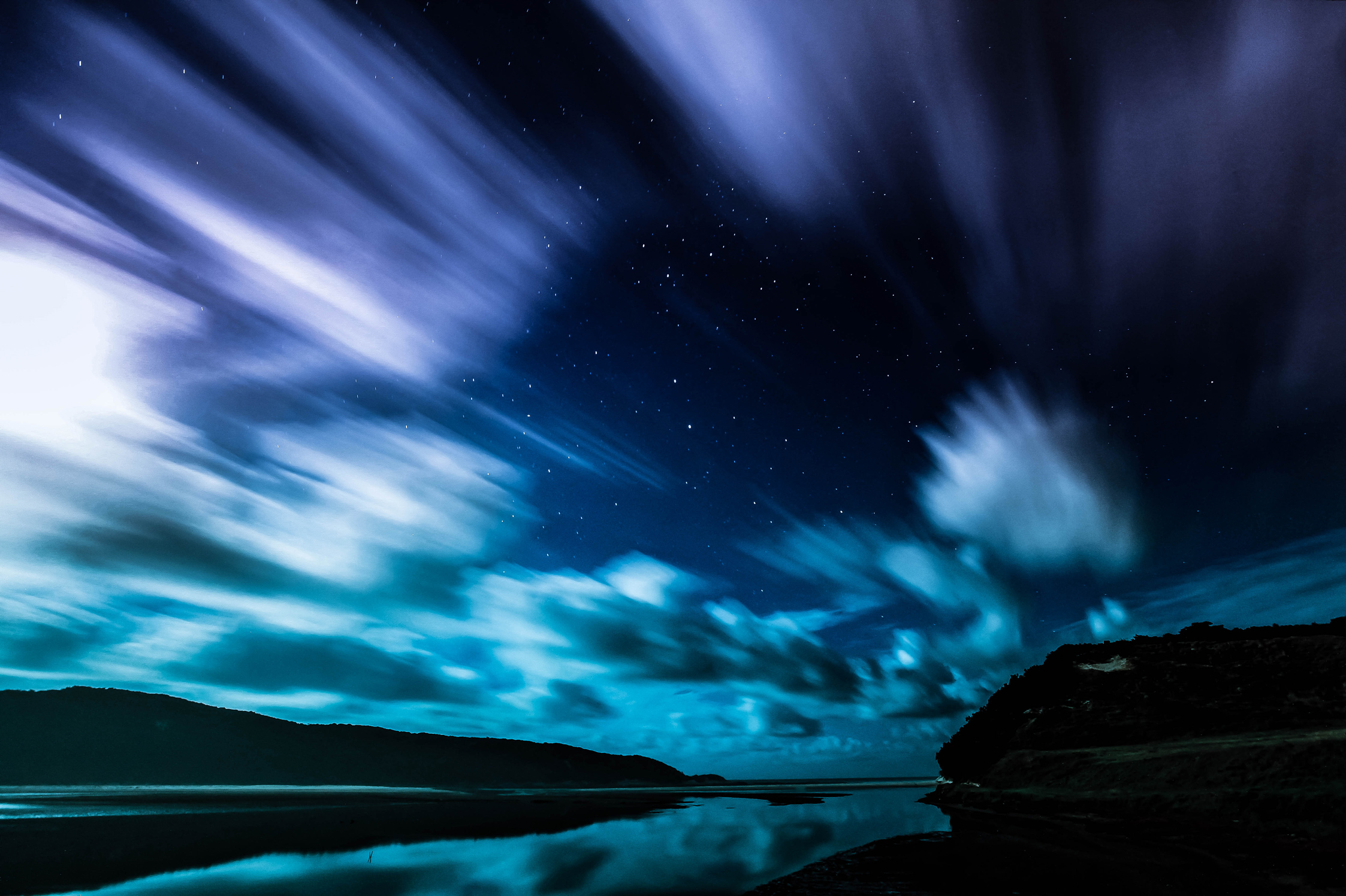 night landscape - stars shining through clouds and clouds reflecting on river - southern cross - long exposure