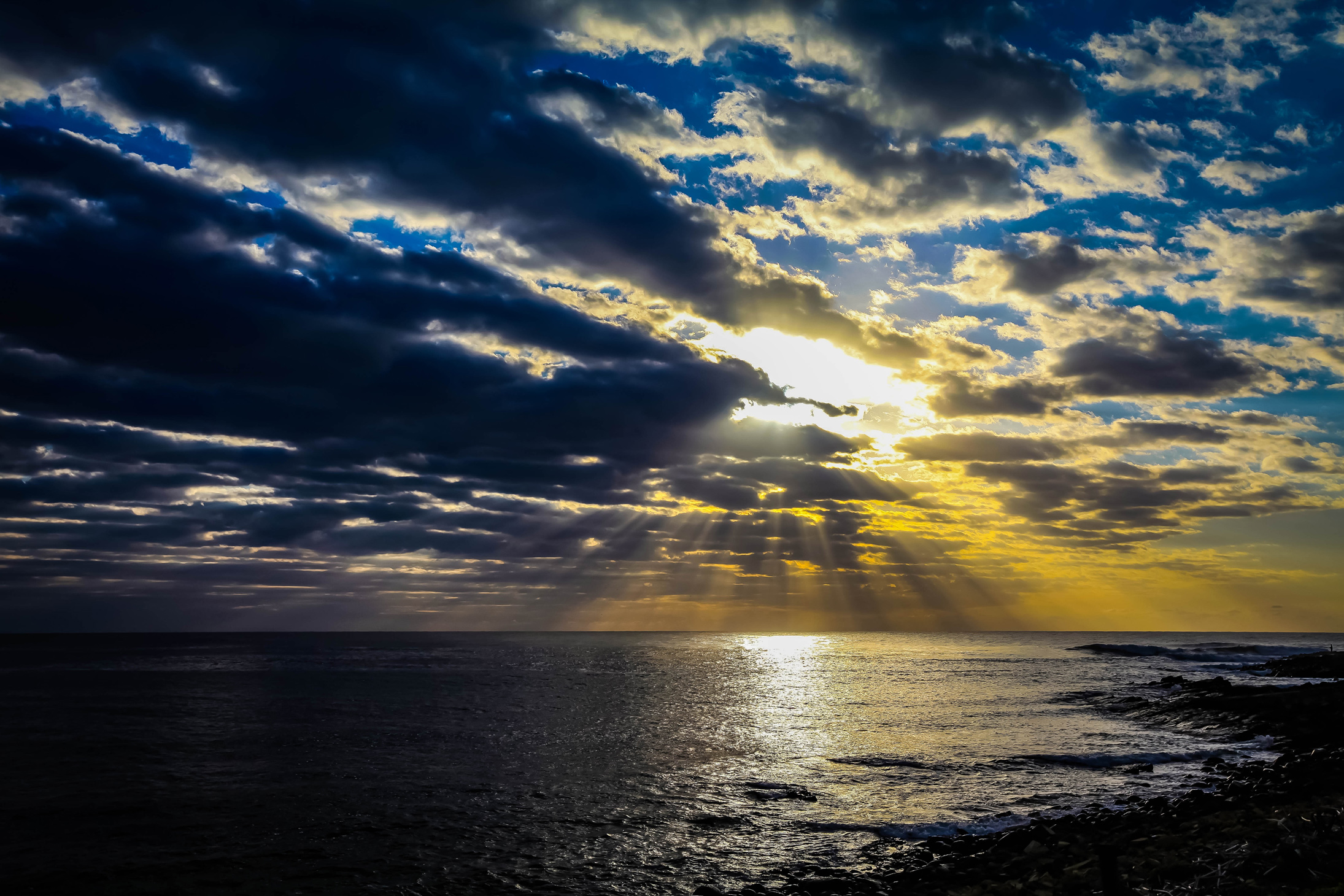 suns rays breaking through clouds onto the ocean - sunset